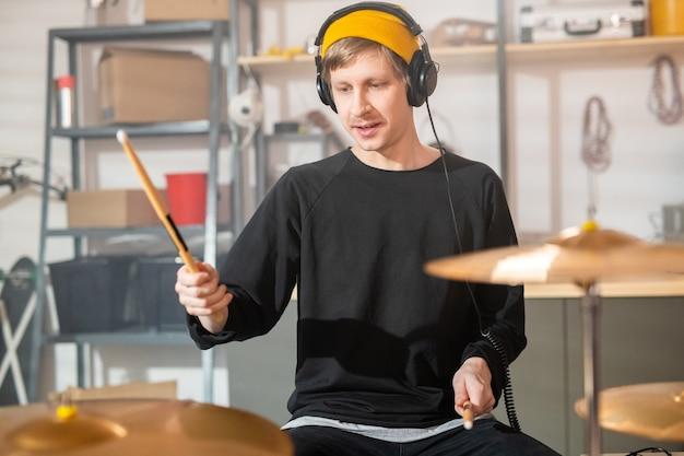 Jeune batteur avec des écouteurs tenant des baguettes sur des cymbales tout en allant battre l'un d'entre eux lors d'une répétition individuelle