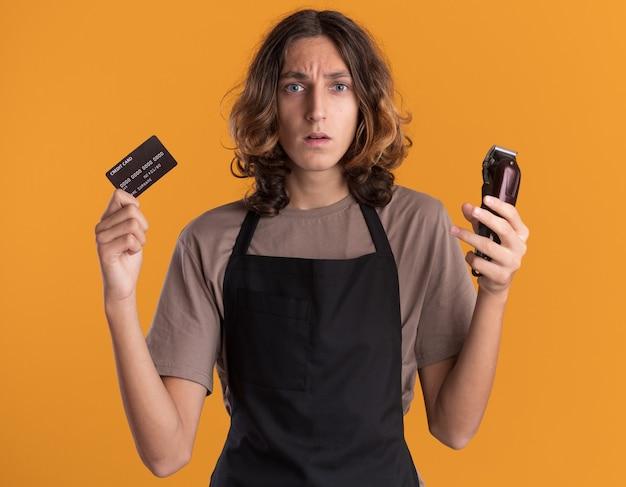 Jeune beau barbier désemparé en uniforme tenant une carte de crédit et une tondeuse à cheveux