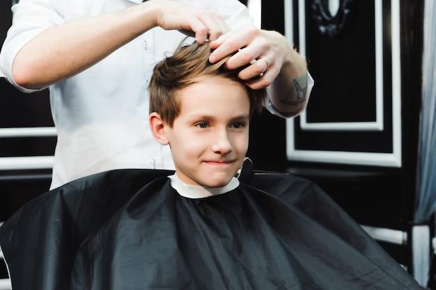 Jeune beau barbier faisant la coupe de cheveux de garçon dans le salon de coiffure