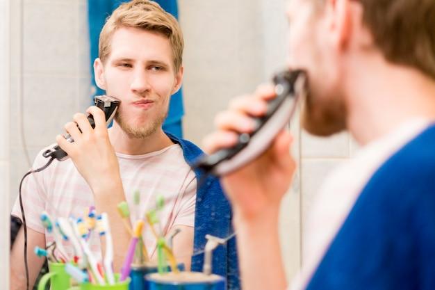Jeune, beau, barbu, avoir, barbe, à, machine, salle bains, regarder, a, miroir