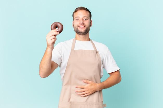 Jeune beau boulanger avec un beignet