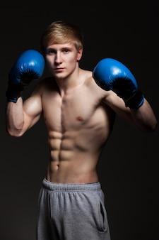 Jeune beau boxeur en gants bleus