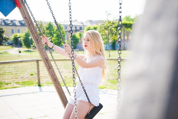 Jeune beau caucasien longue blonde cheveux raides femme s'amuser sur une balançoire dans une aire de jeux