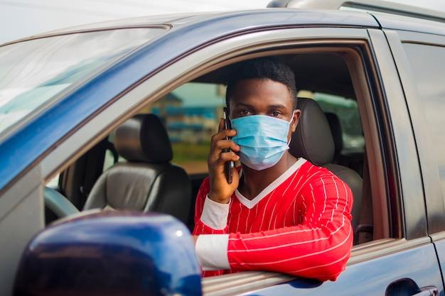 Jeune beau chauffeur de taxi africain portant un masque facial empêchant, prévenant, s'empêchant de l'épidémie dans la société et appelant avec son téléphone portable