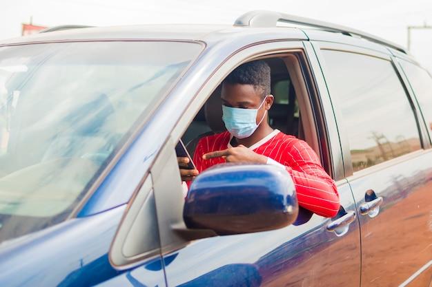 Jeune beau chauffeur de taxi africain portant un masque facial empêchant, prévenant, s'empêchant de l'épidémie dans la société et utilisant son téléphone portable