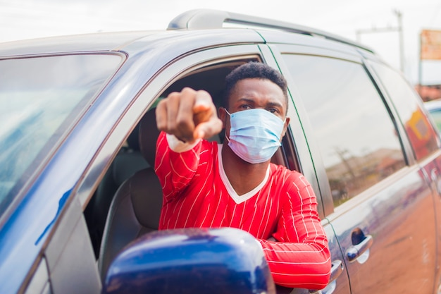 Jeune beau chauffeur de taxi africain portant un masque facial empêchant, prévenant, s'empêchant de l'épidémie dans la société