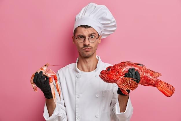 Jeune beau chef tenant des écrevisses non cuites isolées