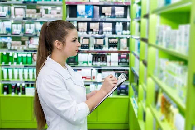 Jeune et beau chimiste contrôle des médicaments en pharmacie