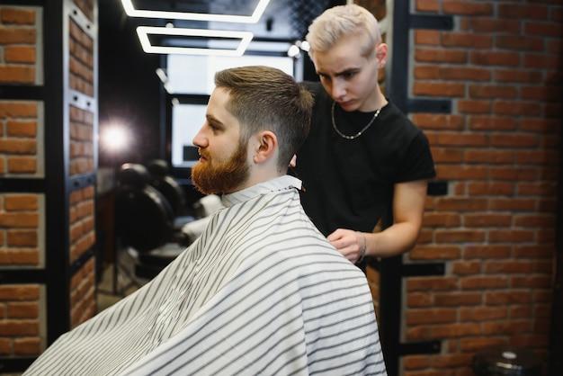 Jeune beau coiffeur faisant la coupe de cheveux de bel homme barbu en salon de coiffure