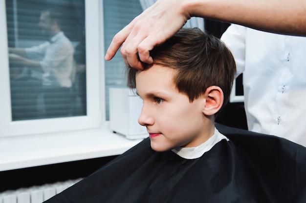 Jeune beau coiffeur faisant la coupe de cheveux d'un garçon mignon dans un salon de coiffure.