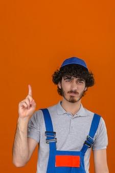 Jeune beau constructeur barbu portant des uniformes de construction et un chapeau fronçant les sourcils bouleversé à cause d'un problème pointant vers le haut sur un mur orange isolé
