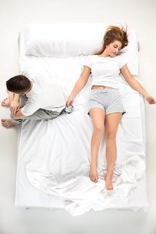 Le jeune beau couple allongé dans un lit avec réveil