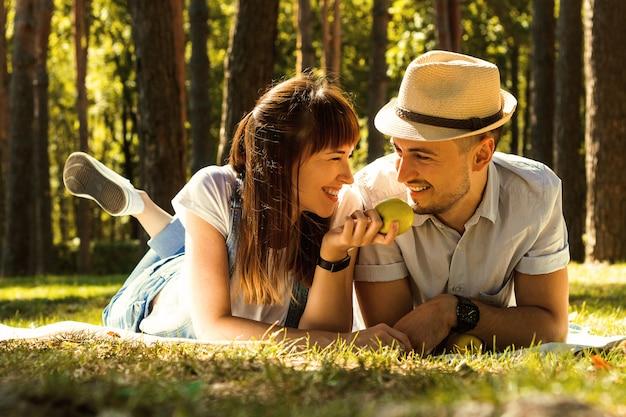 Jeune beau couple allongé sur un tapis dans le parc. pique-nique en famille