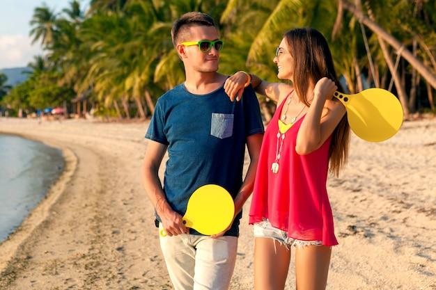Jeune beau couple amoureux jouer au ping-pong sur la plage tropicale, s'amuser, vacances d'été, actif, souriant, drôle, positif