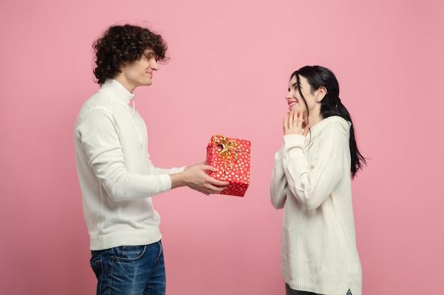 Jeune, beau couple amoureux sur mur de studio rose