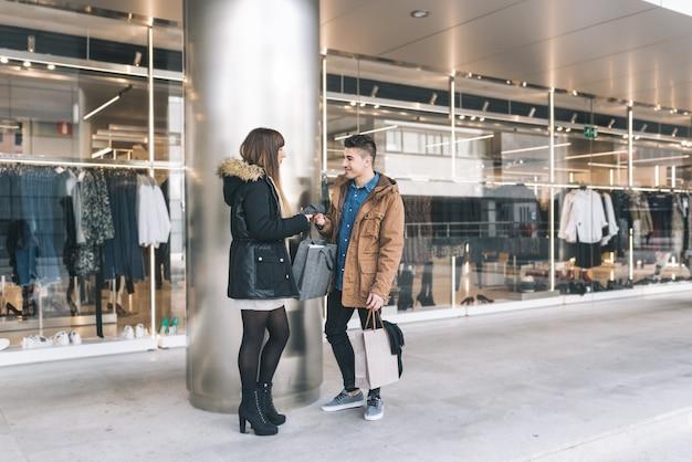 Jeune beau couple amoureux shopping dans la rue
