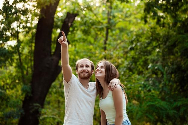 Jeune beau couple au repos, marchant dans le parc, souriant, se réjouissant.
