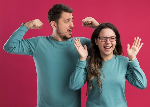 Jeune beau couple en bleu vêtements décontractés homme et femme heureux et excité levant les bras et serrant les poings heureux amoureux ensemble debout sur le mur rose