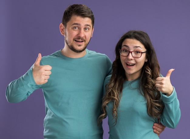 Jeune beau couple en bleu vêtements décontractés homme et femme souriant montrant les pouces vers le haut heureux en amour debout sur le mur violet