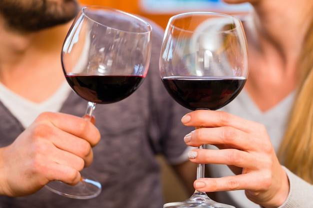 Jeune beau couple buvant du vin rouge à la maison