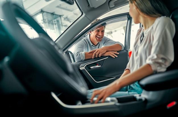 Jeune beau couple choisit une nouvelle voiture. une femme est assise dans une voiture et un homme jette un œil à travers la porte. achat et location de voiture.