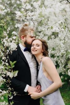 Jeune beau couple dans le jardin dans le contexte de fleurs de cerisier 1
