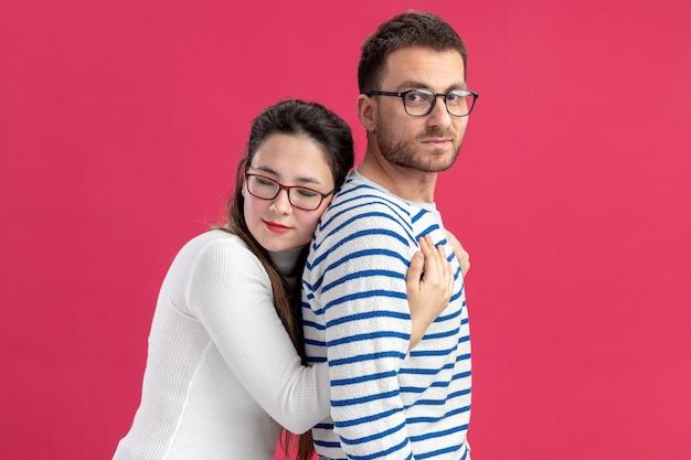 Jeune beau couple dans des vêtements décontractés femme heureuse étreignant son petit ami souriant heureux en amour ensemble célébrant la saint-valentin debout sur fond rose