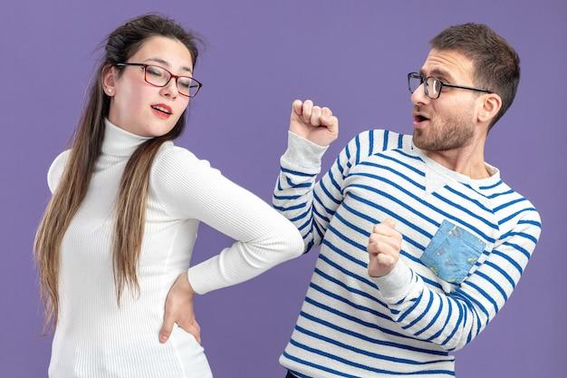 Jeune beau couple dans des vêtements décontractés heureux homme et femme s'amusant ensemble pour célébrer la saint-valentin debout sur le mur violet