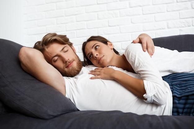 Jeune beau couple de détente au repos allongé sur le canapé à la maison.
