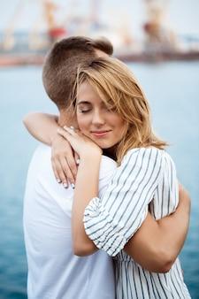 Jeune beau couple embrassant, vue sur la mer.