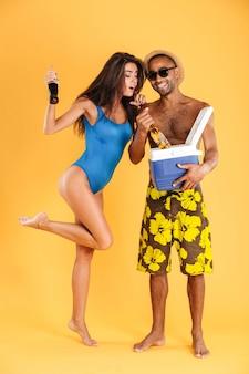 Jeune beau couple d'été heureux tenant des bouteilles en verre et un sac isotherme pour pique-nique isolé sur le mur orange
