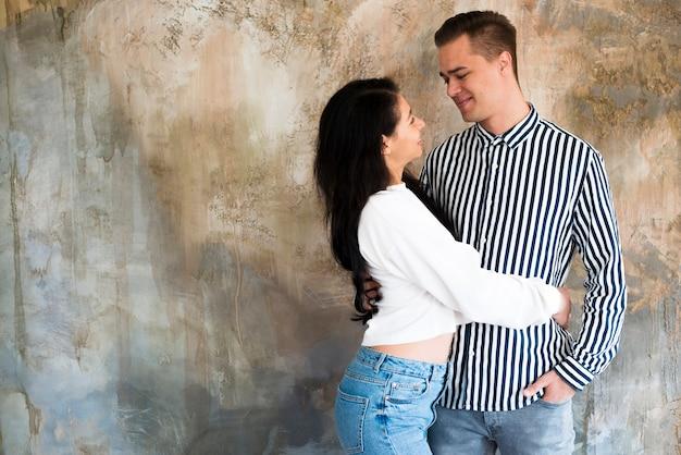 Jeune beau couple, étreindre, contre, mur béton