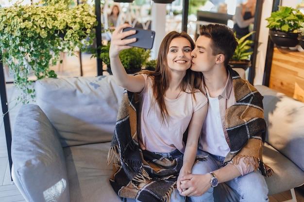 Un jeune beau couple fait un selfie sur la terrasse d'été d'un café moderne