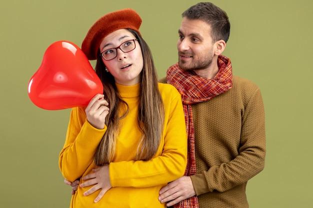 Jeune beau couple femme heureuse en béret avec ballon en forme de coeur et homme heureux avec écharpe célébrant la saint-valentin debout sur fond vert