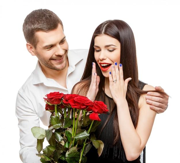 Jeune beau couple avec fleurs sur blanc