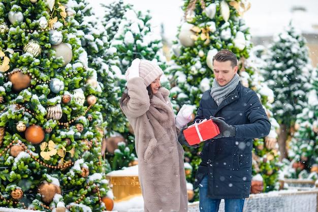 Jeune beau couple gai, fêtant noël dans la rue et offrant en cadeau.