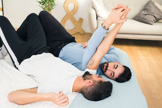 Jeune beau couple gay allongé sur le lit, se tenant la main