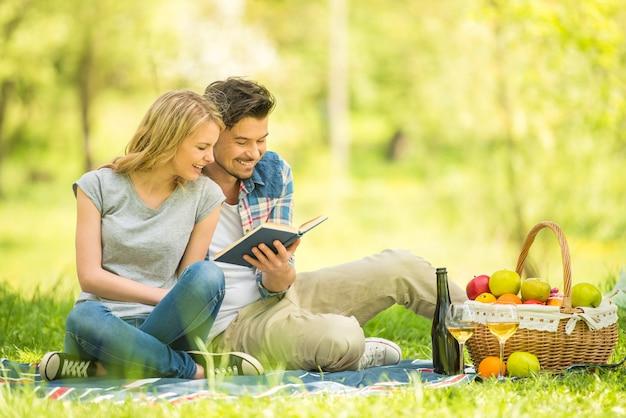 Jeune beau couple habillé décontracté ayant pique-nique dans le parc.