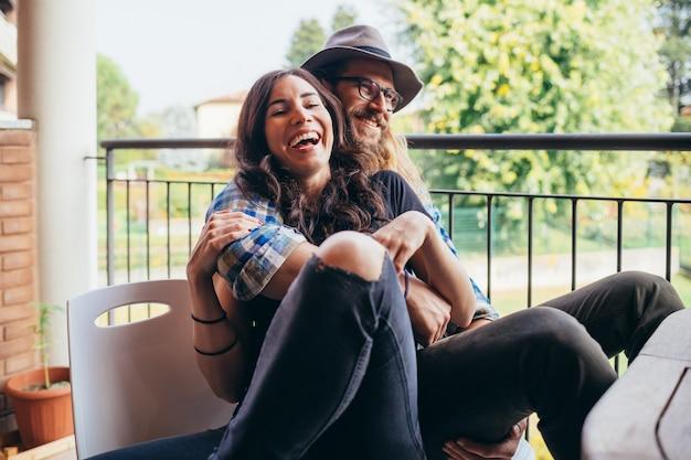 Jeune beau couple heureux assis terrasse extérieure à la maison étreignant
