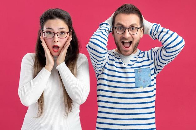 Jeune beau couple heureux homme et femme dans des vêtements décontractés portant des lunettes étonné et surpris célébrant le concept de la saint-valentin debout sur le mur rose