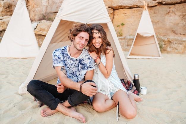 Jeune beau couple hippie souriant assis ensemble et s'embrassant à la plage près de la tente