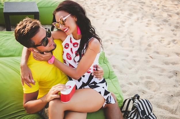 Jeune beau couple hipster amoureux assis sur la plage, écouter de la musique, lunettes de soleil, tenue élégante, vacances d'été, s'amuser, souriant, heureux, coloré, émotion positive