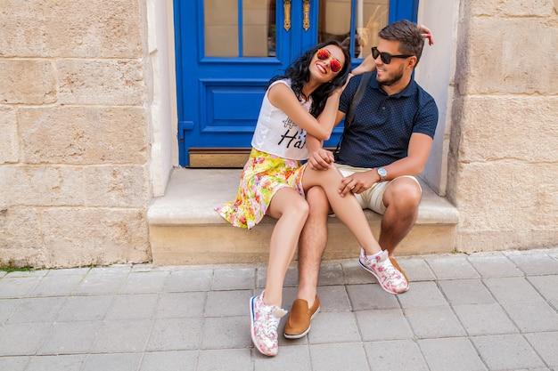 Jeune beau couple hipster amoureux assis sur la rue de la vieille ville