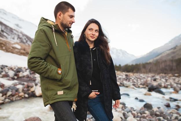 Jeune beau couple hipster amoureux, marchant au bord de la rivière, nature sauvage, vacances d'hiver