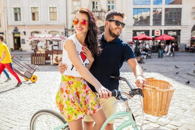 Jeune beau couple hipster amoureux marche à vélo sur la rue de la vieille ville
