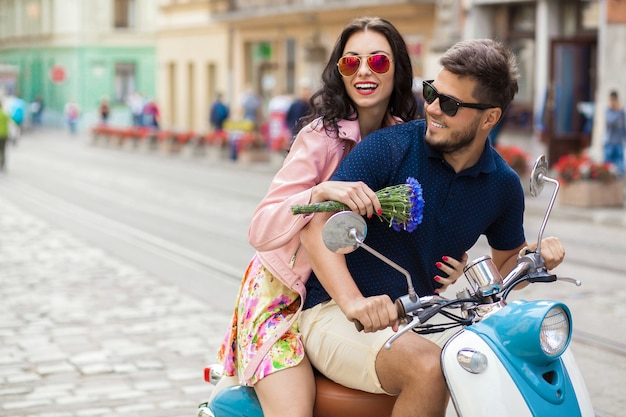 Jeune beau couple hipster à cheval sur la rue de la ville de moto