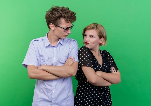Jeune beau couple homme et femme debout dos à dos se regardant en fronçant les sourcils sur le mur vert