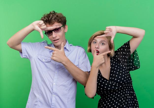 Jeune beau couple homme et femme faisant cadre avec les doigts regardant à travers les cadres sur vert