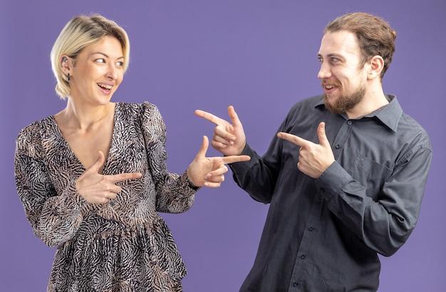 Jeune beau couple homme et femme heureux et gai souriant pointant avec l'index à l'autre concept de la saint-valentin debout sur fond violet