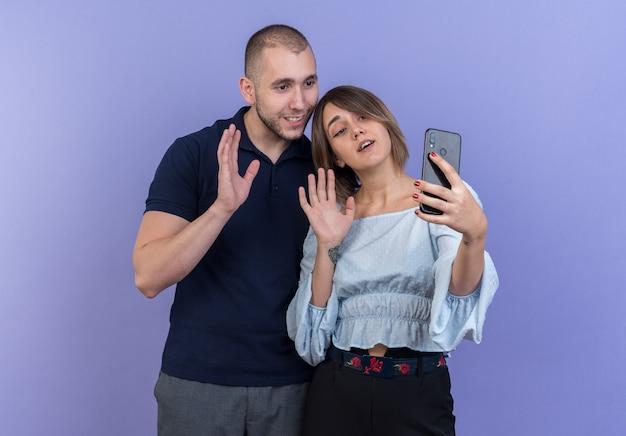 Jeune beau couple homme et femme heureux et positif souriant joyeusement faisant selfie à l'aide de smartphones agitant les mains debout sur le mur bleu